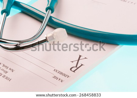 Empty medical prescription with a stethoscope on blue reflective background