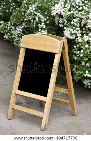 Empty menu board against blooming shrub to add text - stock photo