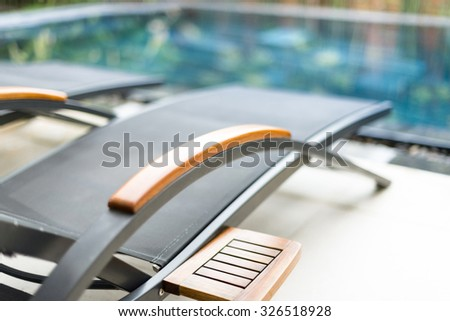 Empty metal chaise lounges in hotel area. Blurry swimming pool with clear water in background. Relaxation and sunbathing on hot day. Summer holidays and vacation on tropical resorts. - stock photo