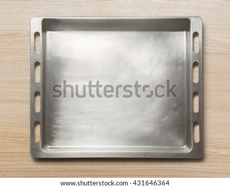 Empty metal oven tray on wooden background