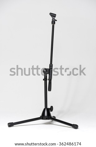 empty microphone stand against a white studio background - stock photo