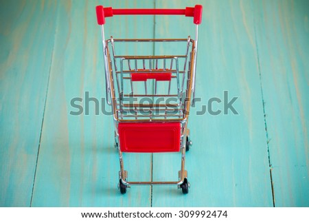 Empty mini shopping cart against wooden background - stock photo