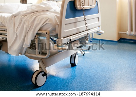 Empty modern hospital bed in a sunny room with a clean blue floor - stock photo