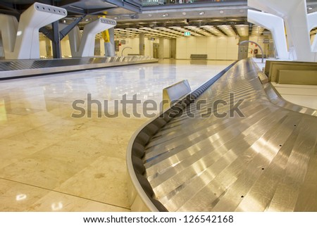 empty modern luggage belt in the airport, focus on belt - stock photo