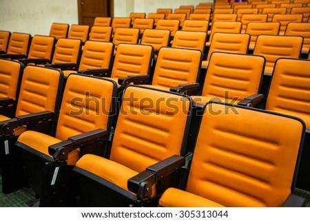 Empty movie theatre chairs background - stock photo