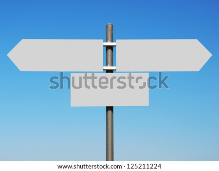 empty multidirectional sign against a blue sky (boards isolated on grey, ready for your design) - stock photo