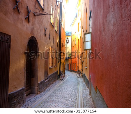 Empty narrow street in the Old Town of Stockholm, with open window and parked bicycles - stock photo