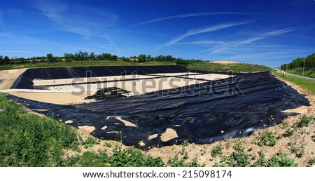Empty new landfill with plastic isolating layer - stock photo