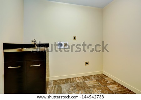 Empty new laundry room with sink and cabinet. - stock photo
