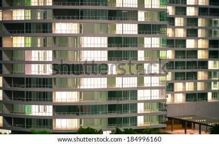 Empty, newly built, modern building at night with lights on - stock photo