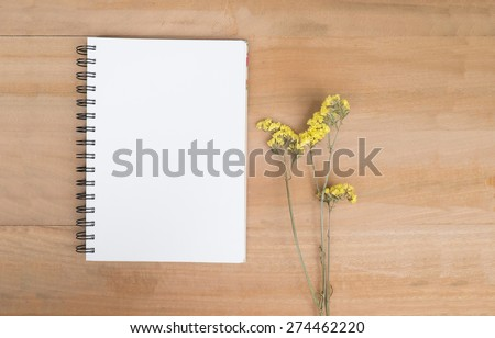 Empty no line note book and yellow flowers on offce desk wooden background. View from above with copy space. - stock photo