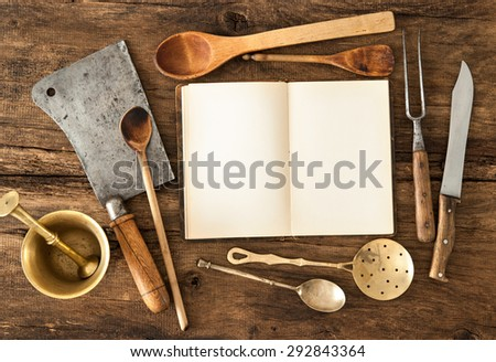 Empty notebook or cookbook and vintage kitchen utensils on wooden table - stock photo