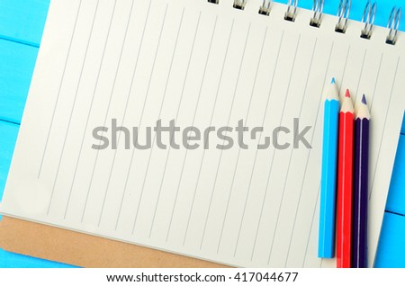 Empty notebook with colorful pencils on blue wooden table