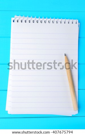 Empty notebook with pencil on blue wooden table