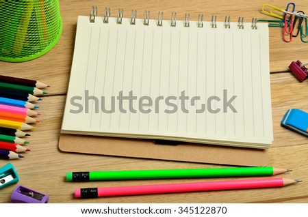 Empty notebook with school accessories on wooden table