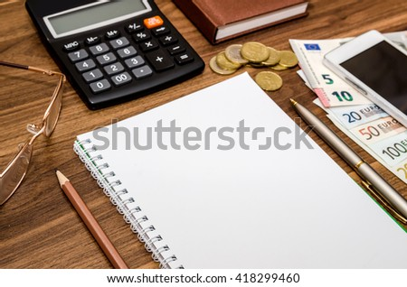 empty notepad with euro money, mobile, calculator and pen on table - stock photo