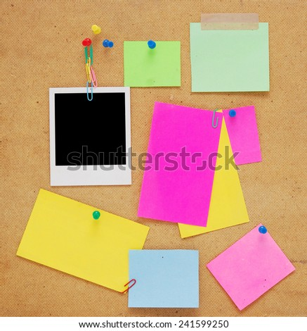 empty notes and photo frame over wooden background - stock photo