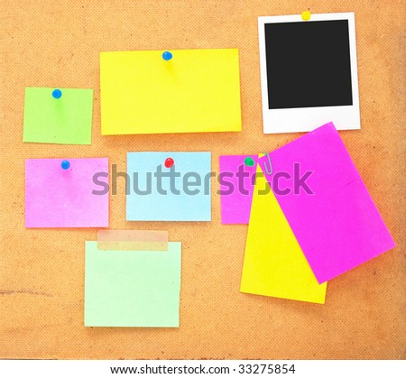 empty notes and photo frame over wooden background