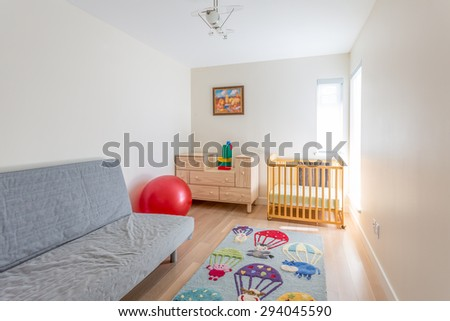 Empty nursery room with a crib, red ball, toys, carpet and couch. - stock photo