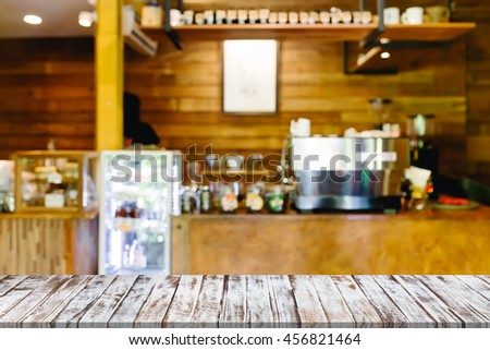 Empty of wood table top on blurred of cafe (coffee shop)  - can be used for montage or display your products