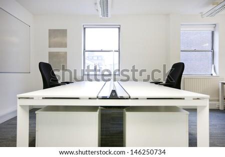 Empty office desks back to back - stock photo
