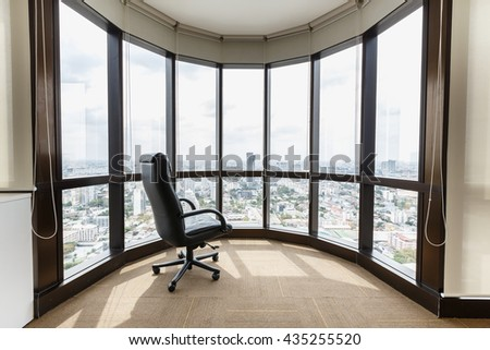 empty office space with large window, And  Black leather armchair - stock photo