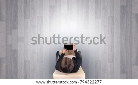 Empty office with woman in a chair and device on her hand