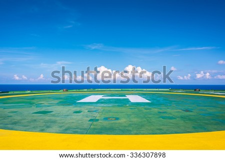 Empty oil rig helipad with few cloud and blue sky, H sign at center in Gulf of Thailand - stock photo