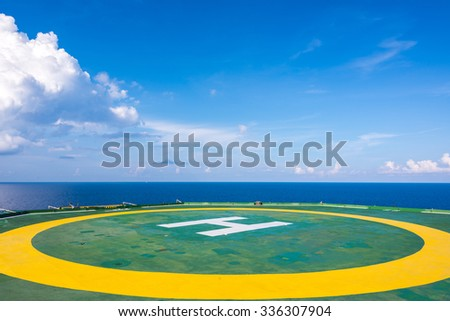 Empty oil rig helipad with few cloud and blue sky, H sign at center in horizon in Gulf of Thailand - stock photo