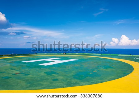Empty oil rig helipad with few cloud and blue sky, H sign left bottom in Gulf of Thailand - stock photo