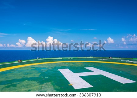 Empty oil rig helipad with few cloud and blue sky, H sign right bottom in Gulf of Thailand - stock photo