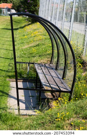 Empty old bench used for substitute players during amateur soccer matches. - stock photo