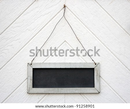 Empty old blackboard sign, hanging on a wooden wall or door
