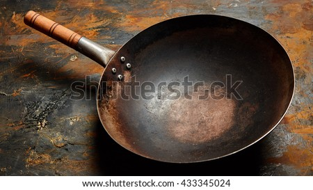 Empty old frying pan with a wooden handle on a rusty metal surface viewed high angle with copy space - stock photo