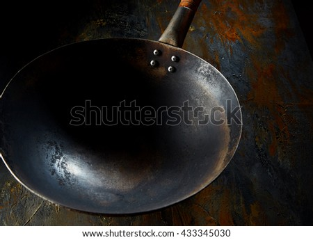 Empty old rusty rustic burnt frying chinese wok with a wooden handle in a close up high angle view for your food placement - stock photo