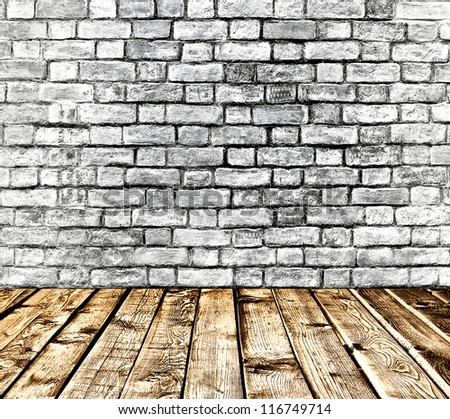 Empty old spacious room with stone grungy wall and wooden weathered dirty floor, vintage background texture of brickwall