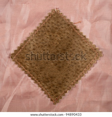 Empty old suede label sewed on brown fabric - stock photo