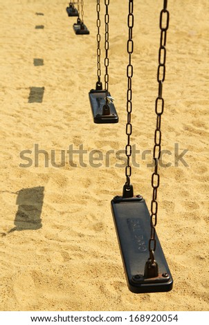 Empty old swing set on sand floor background - stock photo