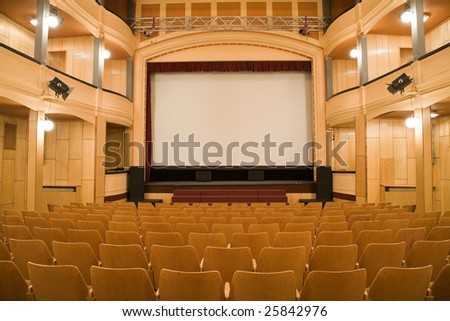 Empty old theater auditorium with arc line of chairs and stage with silver screen. Ready for adding your own picture. - stock photo