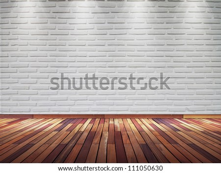 Empty old white brick wall with spot lights and wooden floor - stock photo