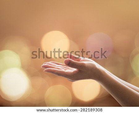 Empty open hands with palms up and candle lights bokeh in warm gold color tone: Female prayer praying warm tone background: Peace of mind mental health concept: Humanity aid: Easter Holy spirit week - stock photo