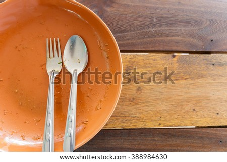 Empty orange dish after food on wooden table - stock photo