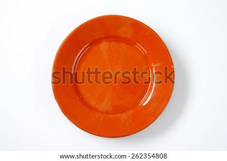 empty orange plate on white background - stock photo