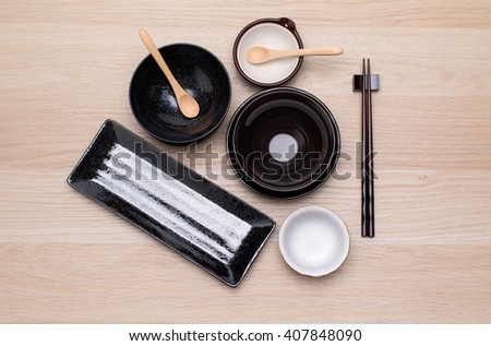 Empty oriental plates and chopsticks on wooden background. - stock photo
