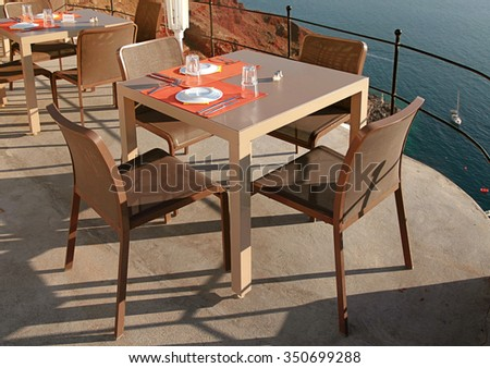empty outdoor cafe with modern tables, chairs and silverware on terrace over sea coast, Santorini island, Greece - stock photo