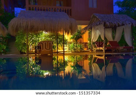 Empty outdoor swimming pool with deck chairs illuminated by warm light. Night time. - stock photo