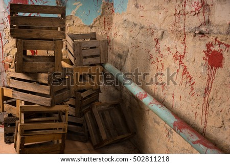 Empty packing crates are arranged one on one in terrible basement in a Halloween horror concept