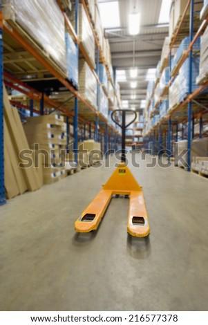 Empty pallet truck in warehouse - stock photo