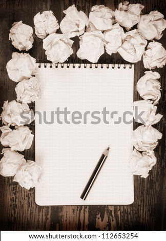 Empty paper, crumpled paper and pencil on wooden table - stock photo