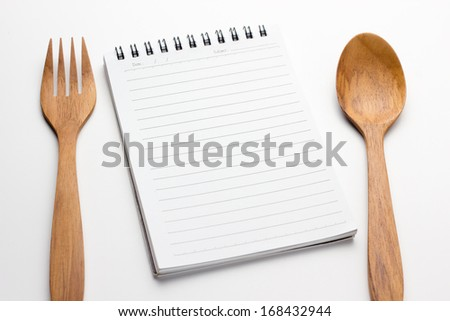 Empty paper for recipe with wooden cooking utensils on kitchen table - stock photo